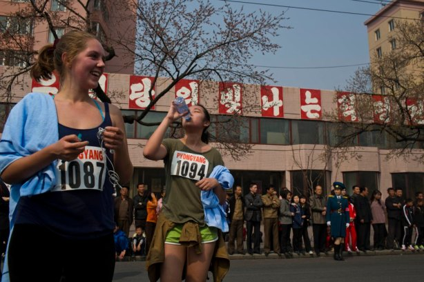 "Tourists who competed in the shorter distance segments of the Mangyongdae Prize International Marathon in Pyongyang, North Korea rest at the end of the race on Sunday, April 13, 2014. From left are Harriet Harrper-Jones, England, and Allie Wu, Taiwan. The sign behind them reads ""Long Live the Shining Revolutionary Tradition of Our Party."" (AP Photo/David Guttenfelder)"