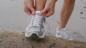 stock-footage-closeup-of-woman-tying-running-shoe-at-beach